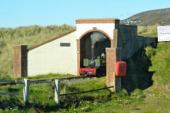 Fairbourne-steam-train-emerging-from-a-tunnel-editorial