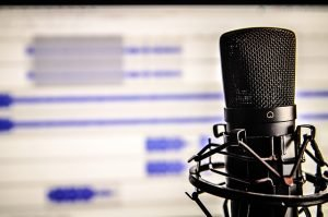 Microphone with audio editing software open in background