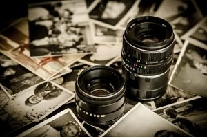 Close up photo of camera lenses and photographs on a table